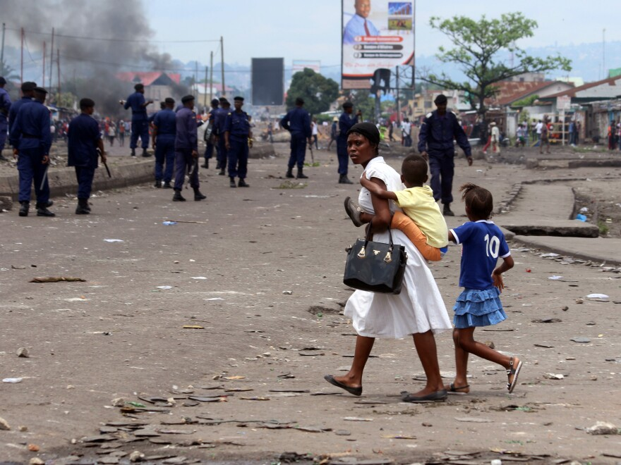 A woman and children pass riot police during a protest against the president in Kinshasa, Democratic Republic of Congo, on Monday.
