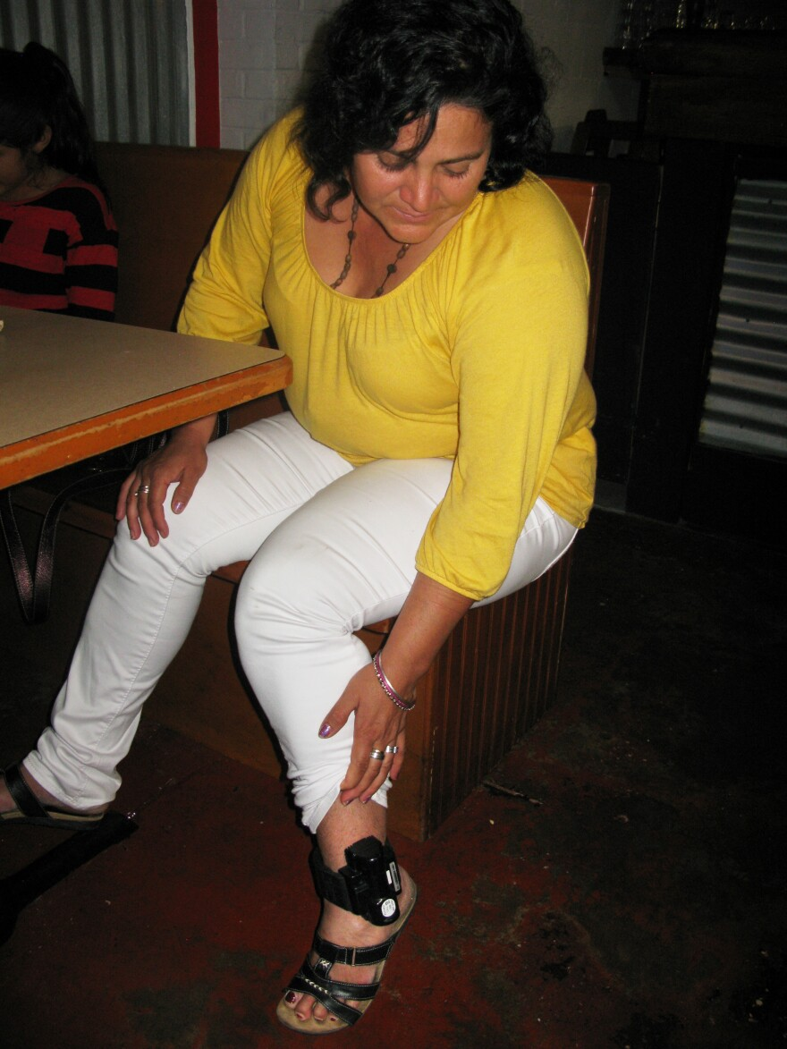 Fresvinda Ponce, a 41-year-old mother from Camayagua, Honduras, shows her ankle monitor. She is living in a shelter in Houston and does not know when authorities will allow the monitor to be removed.