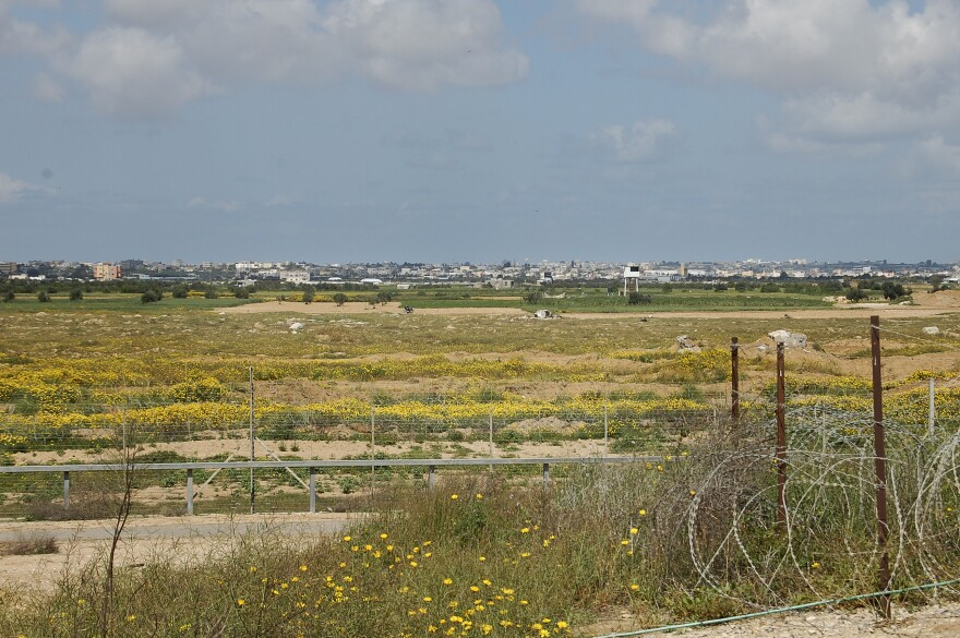 Looking into Gaza from the Israeli side of the fence, soldiers point out a white tower they say is a watch post of the militant group Hamas, and someone they say is a member of the group by a motorcycle in the olive grove at left.