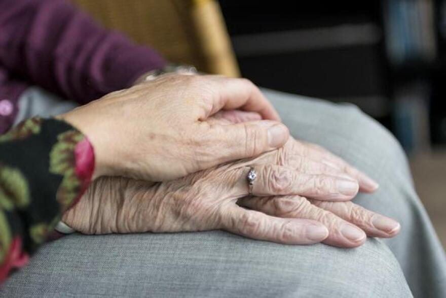 Elderly people holding hands - close-up on hands.
