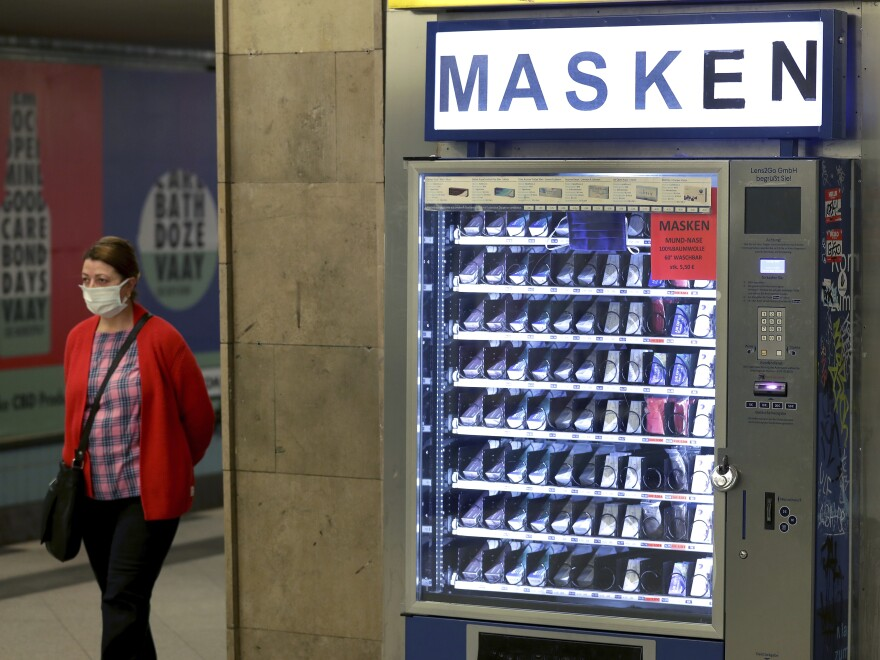 A woman walks past a vending machine that offers washable face masks in a Berlin subway station on Monday. German officials have said they will endorse a decentralized approach to coronavirus contact tracing.