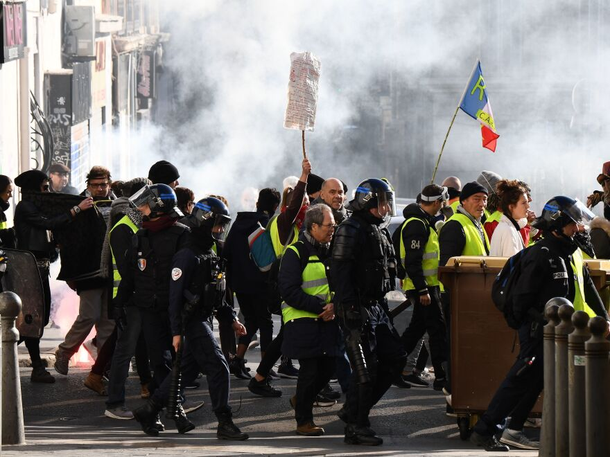 Anti-riot police walk alongside protesters during an anti-government demonstration called by the yellow vest movement in Marseille on Jan. 26.