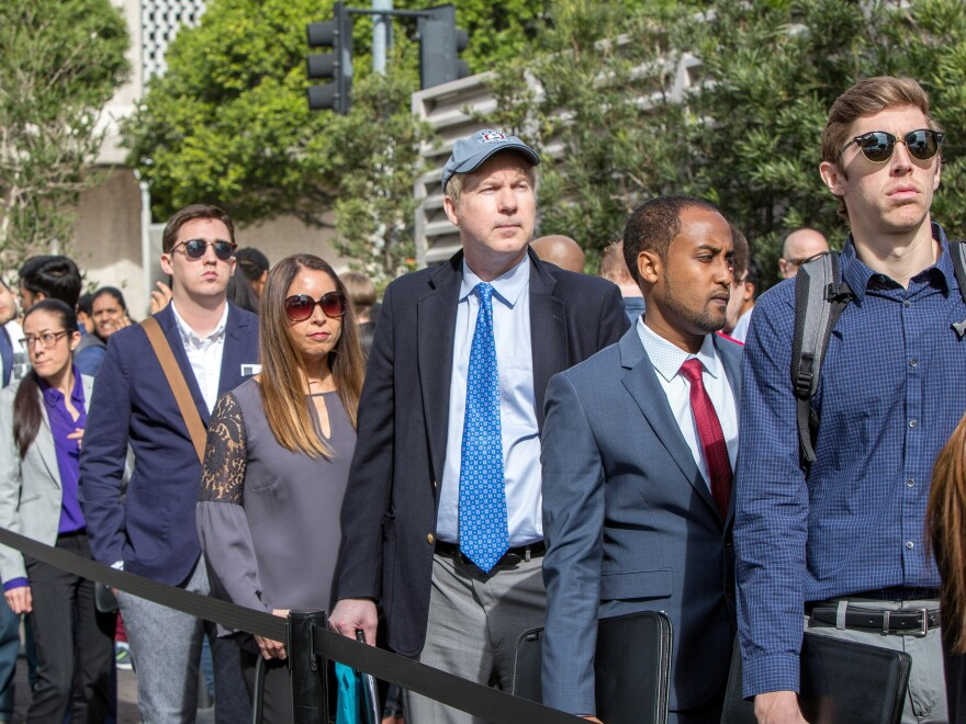 Job seekers line up at a technology fair in Los Angeles in March. Employers added more jobs than analysts expected last month, as the jobless rate remained at a nearly 50-year low of 3.7 percent.