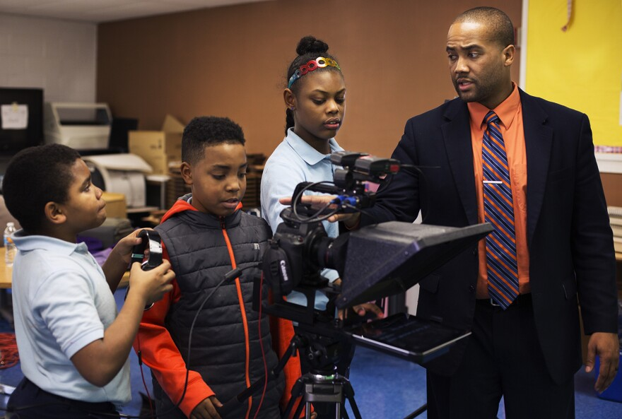 Principal Howard Fields helps Koch TV students set up equipment as they get ready to record a segment.