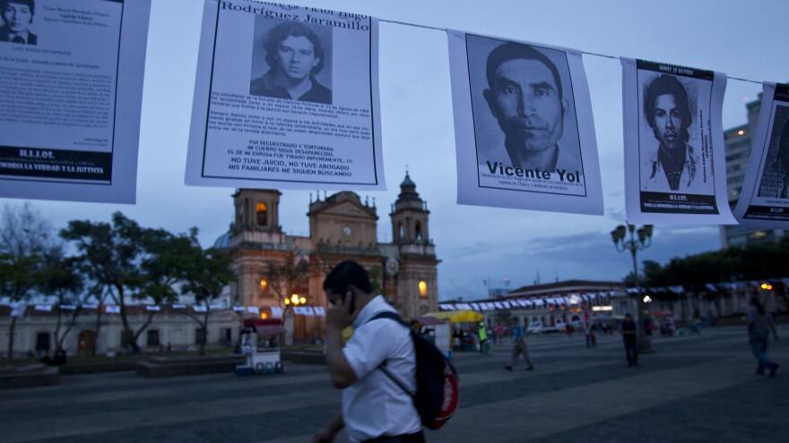 A man walks beside posters with photos showing portraits of missing people, during a march to remember those who disappeared during the Guatemalan civil war, at the Plaza de la Constitution in Guatemala City on June 30, 2016.