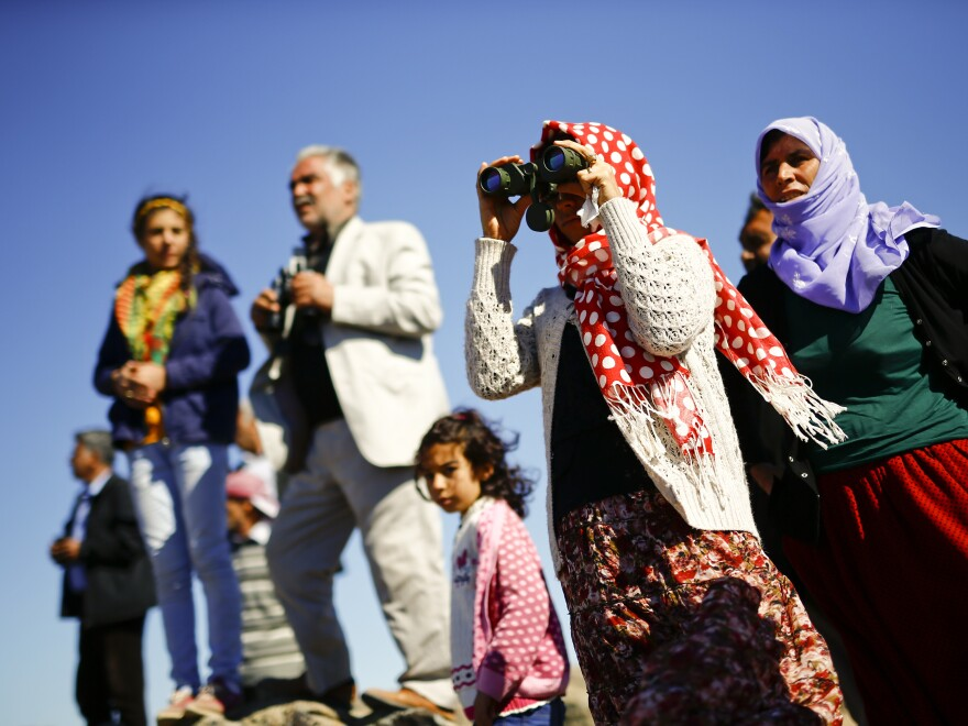 Turkish Kurds watch the Syrian town of Kobani from a hill near the Mursitpinar border crossing on Monday.
