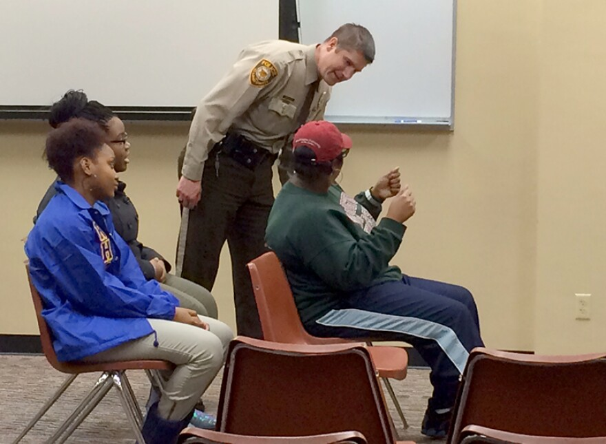 A St. Louis County Police officer participates in a model traffic stop with attendees of the law enforcement forum.