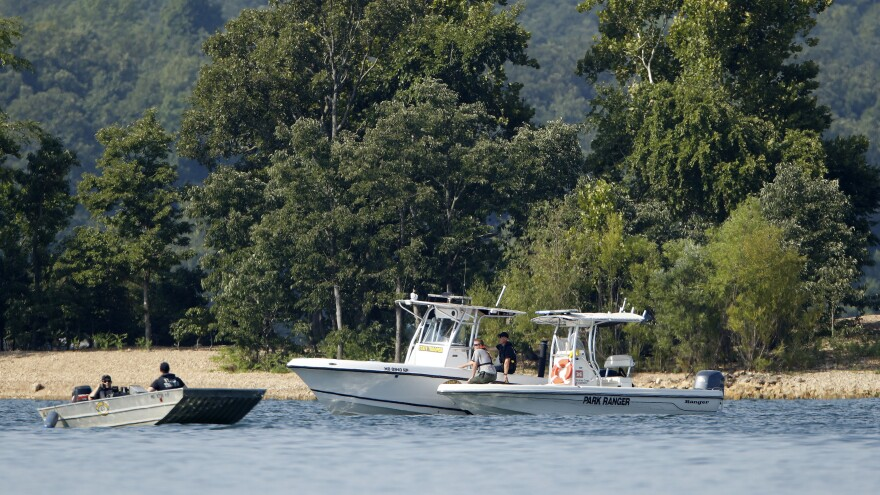 Emergency workers patrol an area of Table Rock Lake in Branson, Mo., on Friday, a day after a duck boat capsized and sank during a storm. Authorities say 17 people died in the accident.