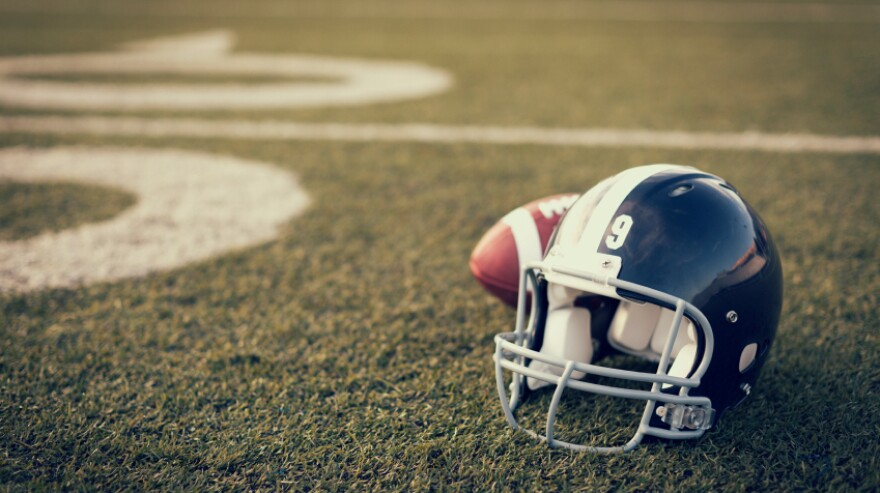A football helmet and football on the football field.