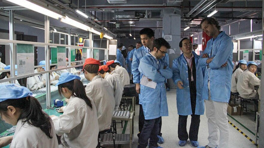 Bas van Abel, at right in the blue coat, visits the production partner, Guohong, in China in 2013.