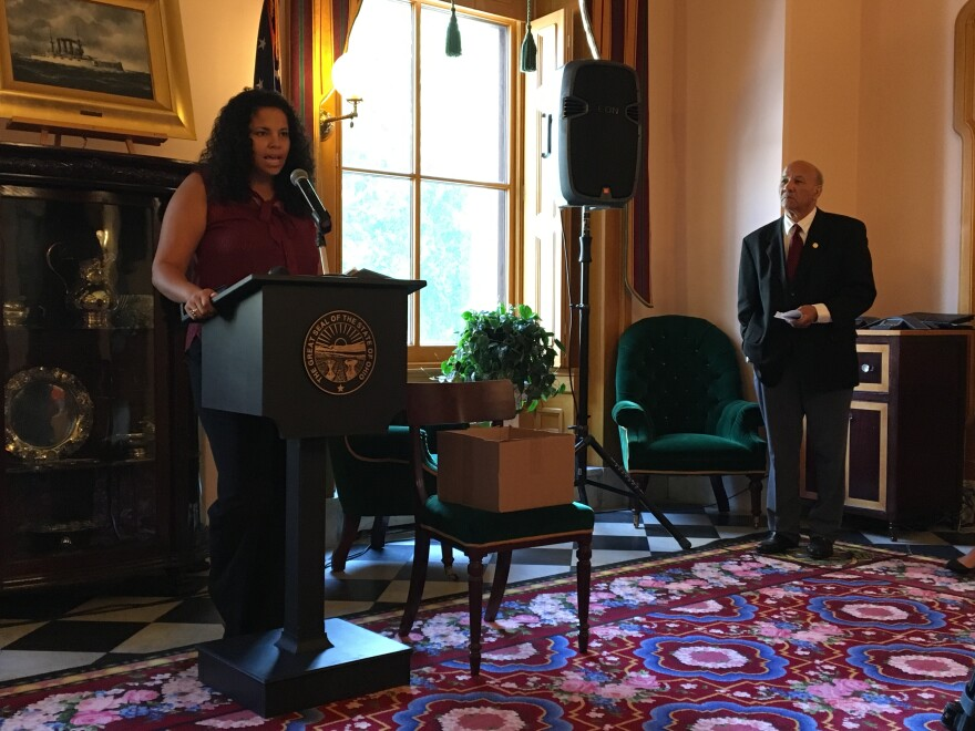 Bianca Edwards speaks at a press conference regarding AT&T's request to drop out of the Lifeline program, as Tom Roberts, the Ohio Conference NAACP president, looks on