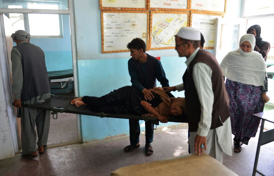 Afghan volunteers carry an injured woman on a stretcher to a hospital in Ghazni province on Sunday. The Taliban assault on the city of Ghazni has resulted in intense gun battles and hundreds of casualties.
