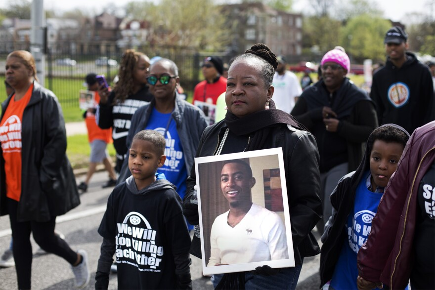 Lisa Woods marches against gun violence with a photo of her son, Kendrick Woods, who was killed in 2017 at the age of 19.