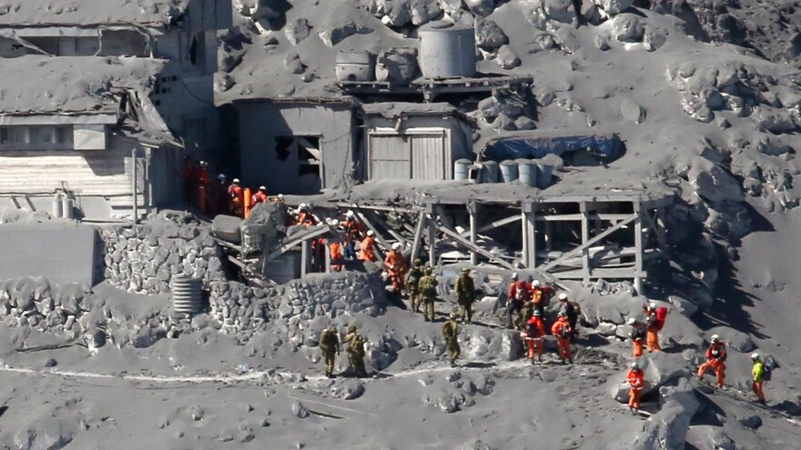 Rescue workers and Self-Defense Force soldiers search for missing climbers and survivors among ash-covered mountain cottages on the top of Mount Ontake in central Japan.
