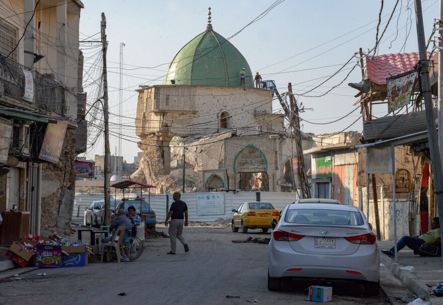 People walk near Mosul's heavily damaged Al-Nuri Mosque, where Baghdadi announced the launch of a caliphate in 2014.