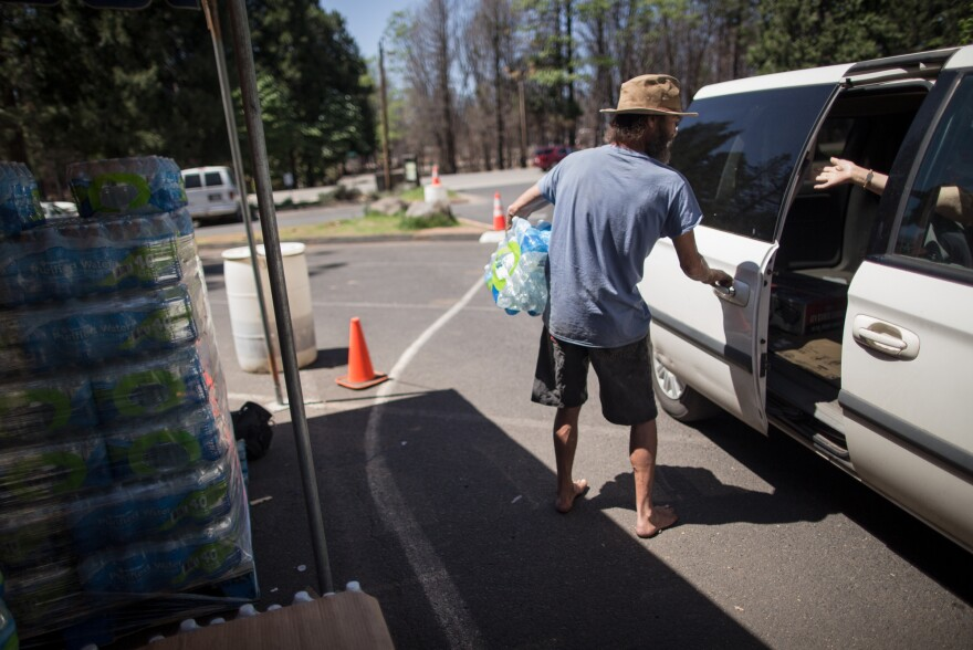Damian Cuypers hands out free water to residents at the Magalia Pines Baptist Church just outside Paradise. Private citizens and groups have been volunteering and providing food and water since the fire.