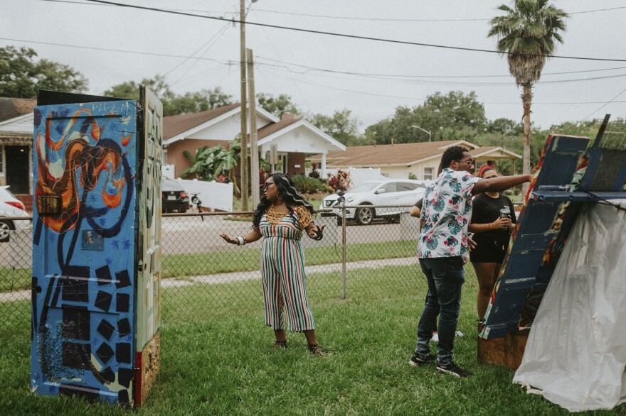 Artists Shawana Brooks and her husband, Roosevelt Watson III, talk to visitors at the 6 Ft. Away Gallery, an art space they created in their yard.