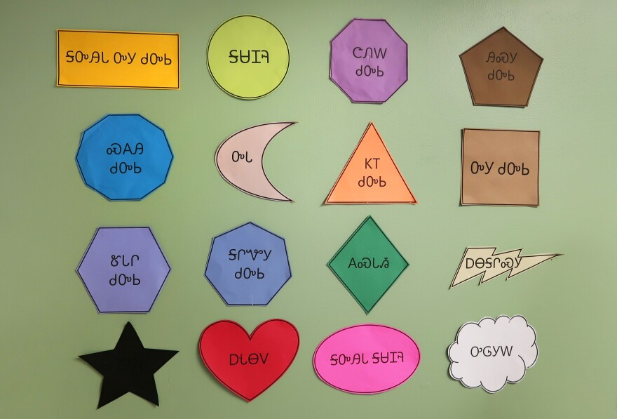 A wall at the New Kituwah Academy shows cutouts of shapes with their corresponding names written in Cherokee.