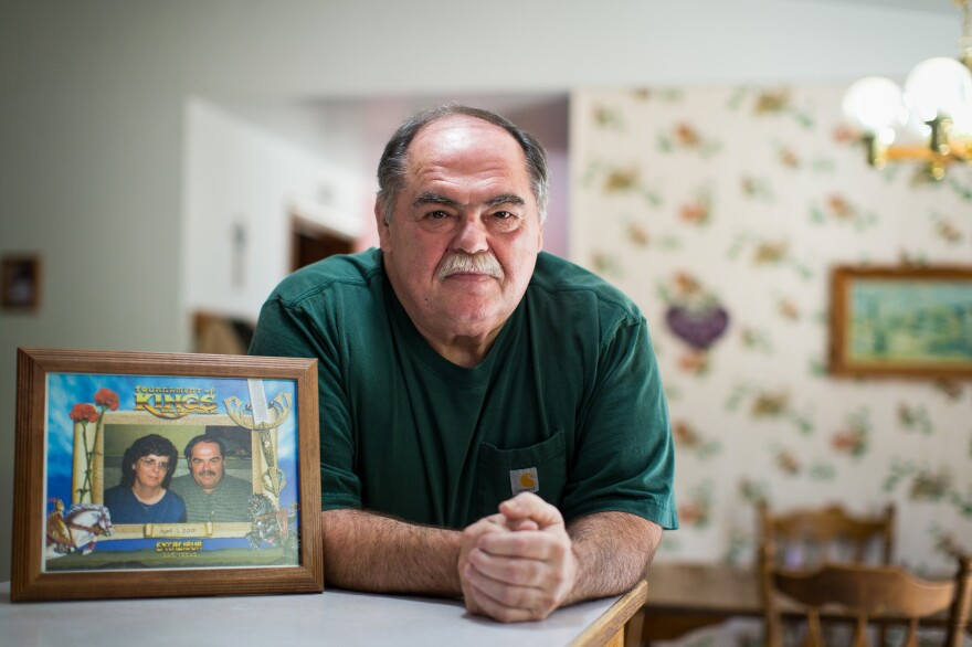 Mike Clapshaw poses with a picture of him and his wife, Deborah, in his Port Angeles, Wash., home.
