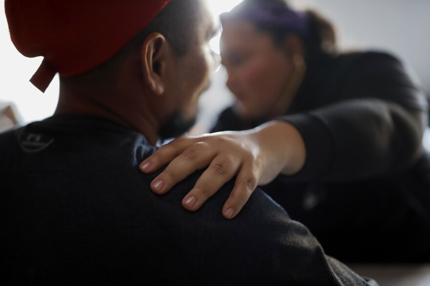 In this Dec. 14, 2019, photo, Dr. Psyche Calderon works with a patient in a migrant shelter in Tijuana, Mexico. Calderon is a general practitioner volunteering to provide care for Central Americans stuck in Mexico while they try to obtain asylum.
