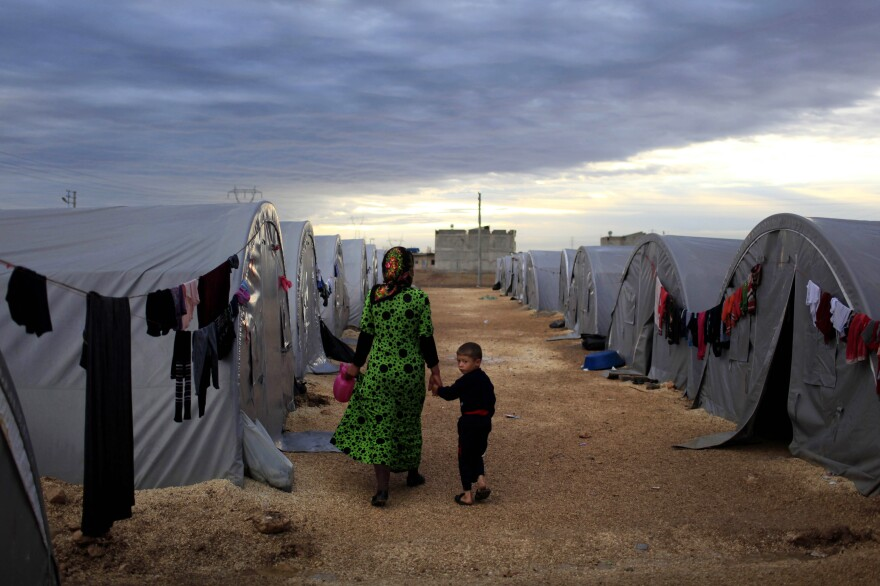 A Kurdish refugee mother and son from the Syrian town of Kobani walk beside their tent in a camp in the southeastern town of Suruc on the Turkish-Syrian border in 2014 in Sanliurfa, Turkey. President-elect Joe Biden aims to reverse the Trump administration's dramatic cuts to refugee admissions.