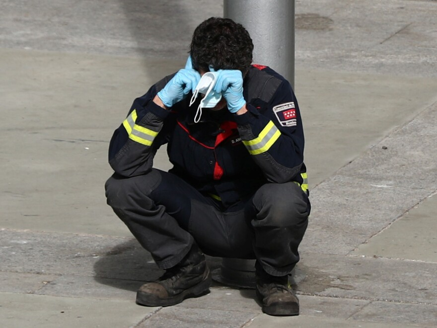 A firefighter takes a moment to rest outside a temporary hospital in a conference center in Madrid, Spain, that was set up as an overflow area for COVID-19 patients. More than a million coronavirus cases are now reported worldwide, putting intense pressure on health and emergency workers.
