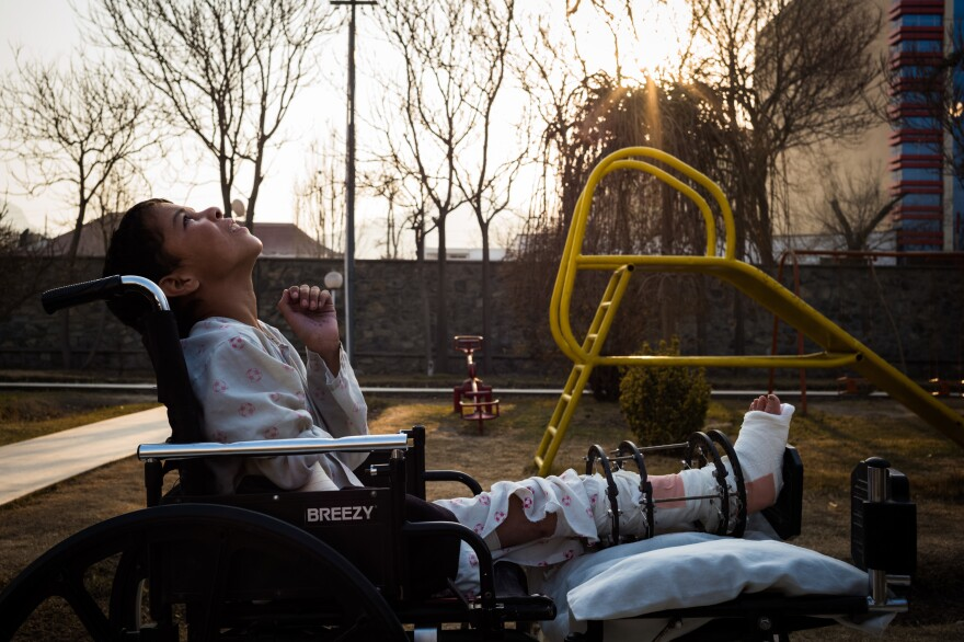 Barkatullah sits in his wheelchair and looks up at a passing helicopter. He's on the playground at the hospital where he's being treated. He's not able to use the equipment because of his injuries.