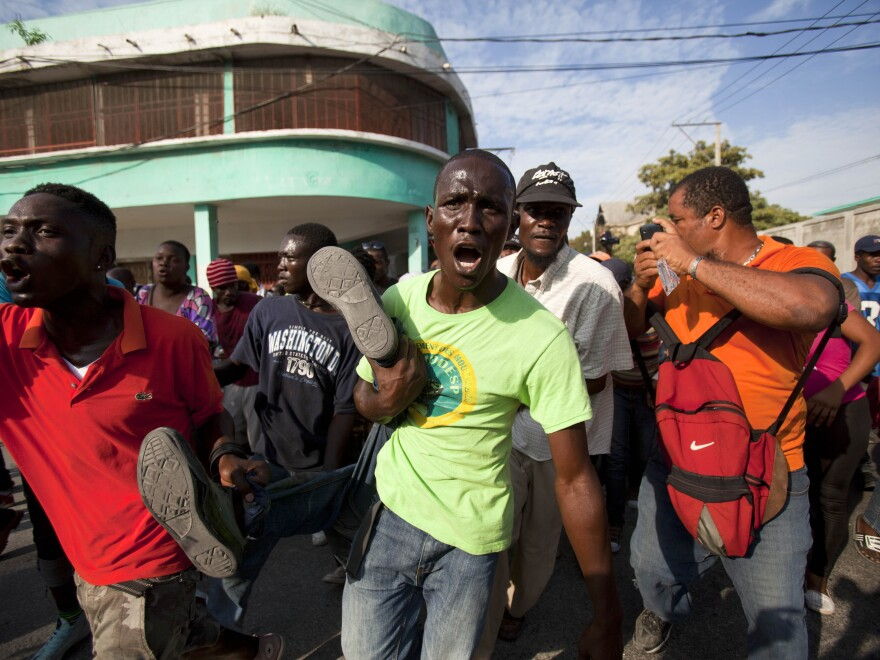 Anti-government protesters carry the body of a demonstrator who was shot to death during clashes with the National Police in Port-au-Prince, Haiti, on Saturday. Prime Minister Laurent Lamothe says he will step down in response to protesters' demands.