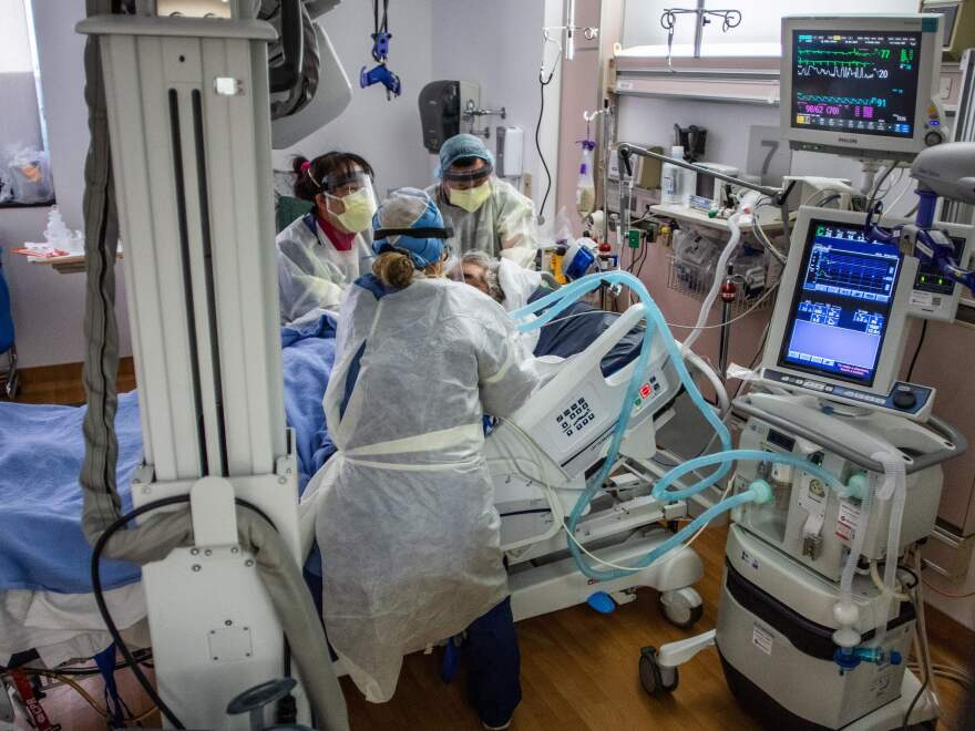 Physicians and nurses wear personal protective equipment while they attend to a COVID-19 patient in the ICU at Providence Cedars-Sinai Tarzana Medical Center in Tarzana, Calif. on December 18, 2020.