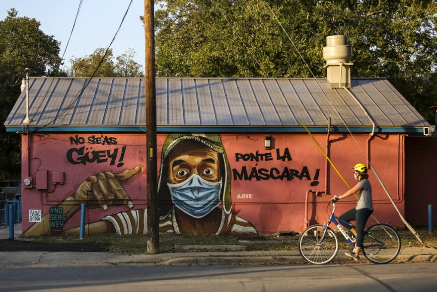 """A cyclist passes a Spanish language mural, featuring the popular Mexican television actor Chespirito, reading """"put on the mask"""" on Marcelino's restaurant in East Austin."""
