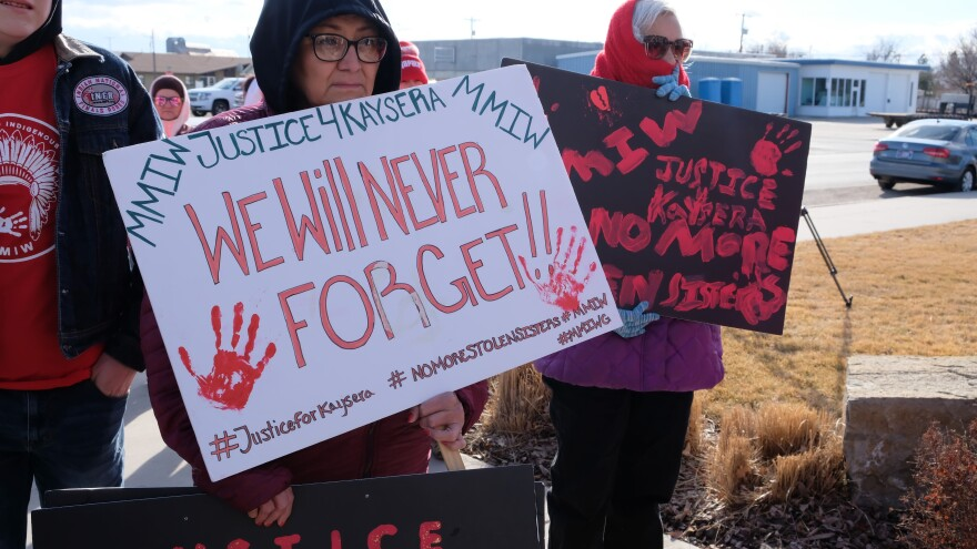 "A woman holds a sign covered in red hand prints that reads ""We will never forget."""