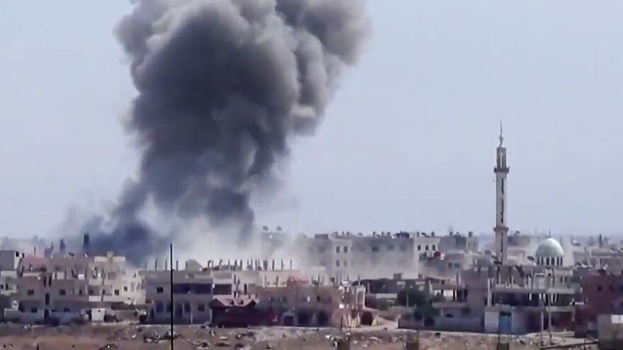 Smoke from heavy shelling rises above buildings in Dara'a, Syria, on Aug. 28.