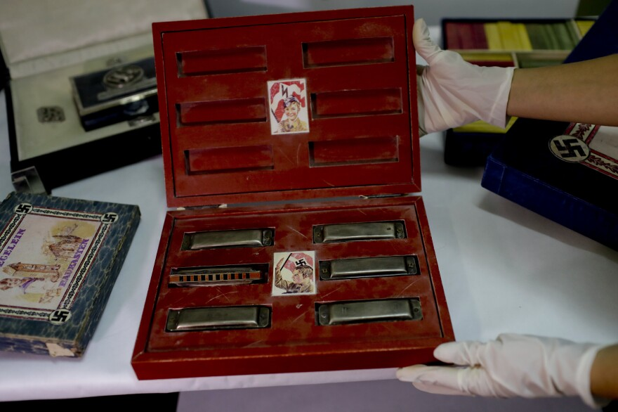 The trove included toys used to indoctrinate children, such as this box marked with swastikas and containing harmonicas.