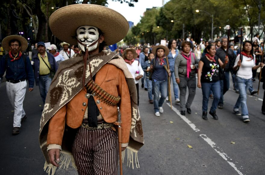 In Mexico City on Wednesday, people march to demand justice for 43 missing students. Mexican authorities ordered the arrest of the mayor of Iguala and his wife in connection with the attack.