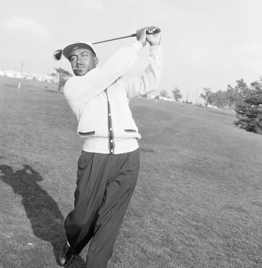 Charlie Sifford works out at a course in Los Angeles in 1957 after winning $11,500 in the Long Beach Open. Sifford helped break the color barrier in the PGA.