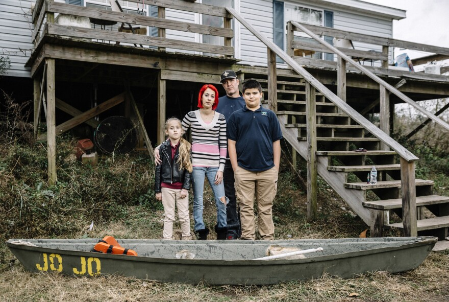 Ollie and Daniel Williams stand in front of their raised home with their children Trinity, 9, and Masen, 12. The land surrounding their house floods so often that the family keeps a small fiberglass canoe tied to the bottom of the front steps and a flat-bottom boat tied to the side of their house to aid in evacuating.