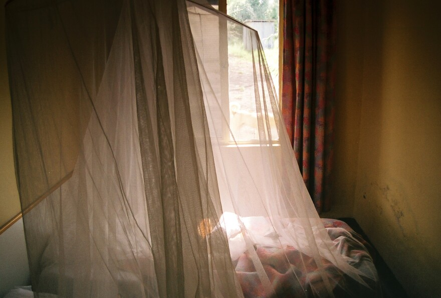 Nets lay drapped over a bed to protect against mosquitos.