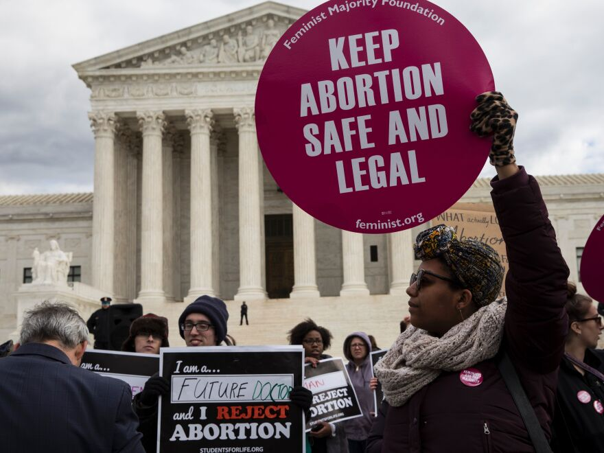 Abortion rights supporters and opponents protest outside the Supreme Court last year. The issue of abortion will spark millions of dollars in spending on advocacy for and against President Trump's Supreme Court nominee.