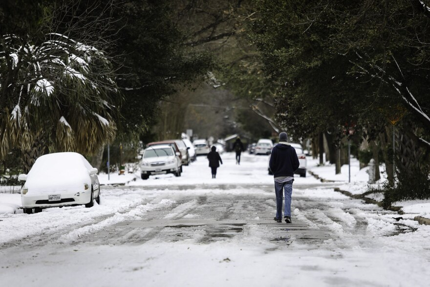 People walking through the empty snow, covered-streets of Austin's Hyde Park neighborhood on Tuesday.
