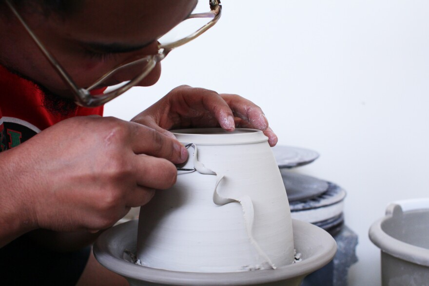 Kahlil Irving, 24, hunches over a clay vessel as it spins on a wheel. He smooths the sides, with his face an inch or two away from the turning.