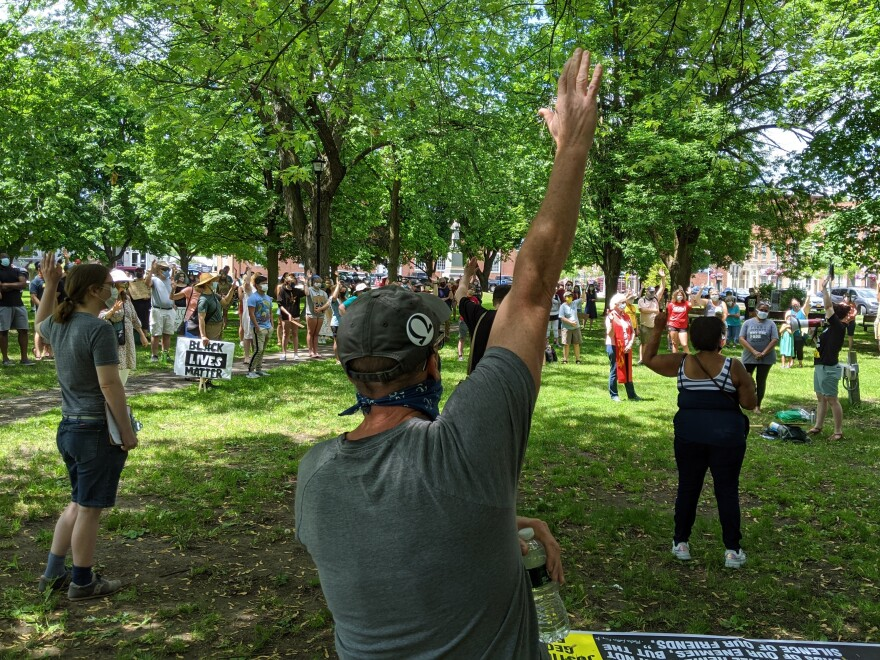 Hands shoot up after a speaker asks if people have ever heard someone say something racist but done nothing about it at a rally in Canton, N.Y. Saturday.