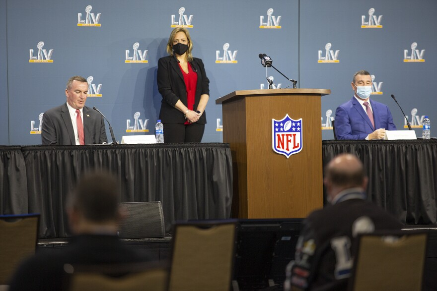 Security officials seated at mics with a large NFL podium in the foreground and a Super Bowl LV background.