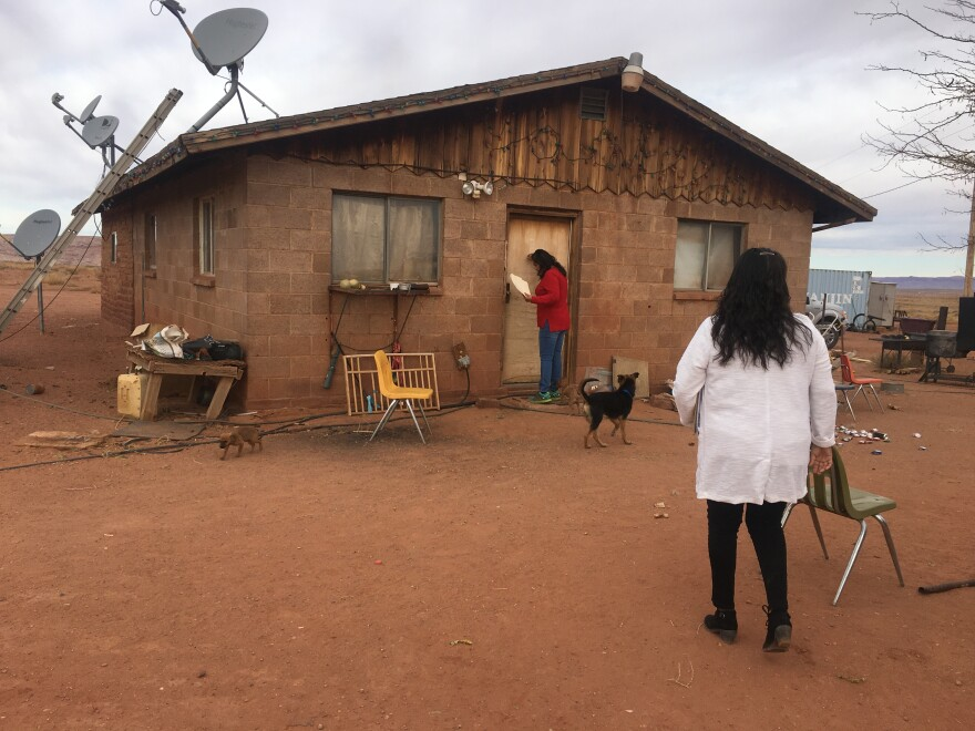 Two women walk up to a house with dogs running around on red dirt ground.