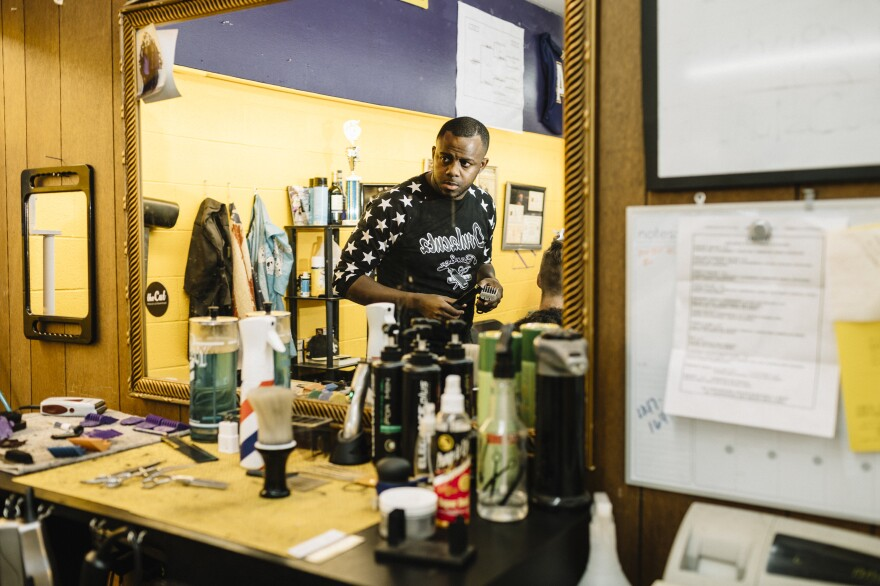 Justin Boyd, 32, cuts a customer's hair at New Age Barber Shop in downtown Oakdale, La. During an average week before the shutdown, Boyd says, he would give about 20 to 25 haircuts per day and clear about $300. Since the shutdown, that has dropped to $180 on a good day.
