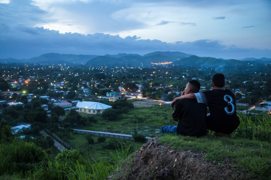 "Moises, 17, left, and Jaime look down on the patchwork of neighborhoods outside San Pedro Sula, a city in Honduras where gang rivalries play out. The violence is so bad that ""no one goes in"" the neighborhoods, says photojournalist Tomas Ayuso. ""Food delivery trucks, ambulances don't want to go in because they're afraid something will happen."""