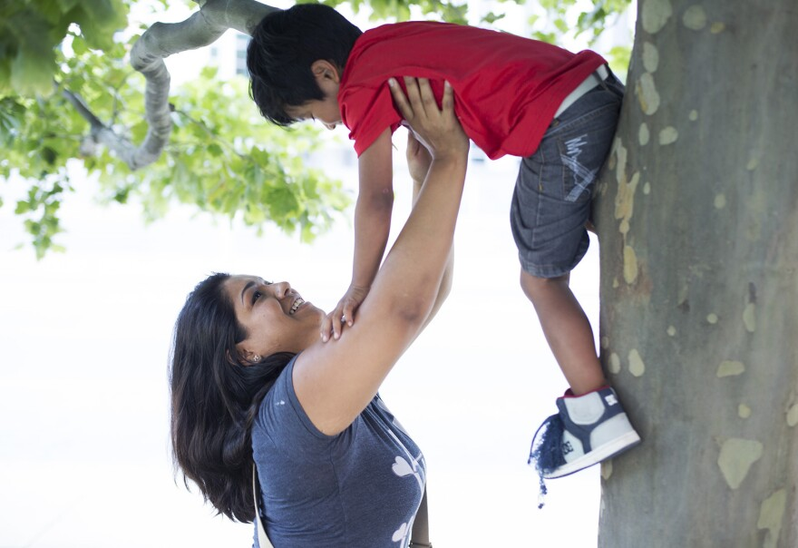Mariana Flores helps her son, Jitzak, climb a tree after a rally in support of immigration in reform in June.