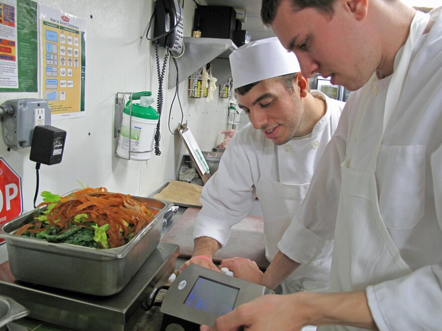 Glen Osterberg (right) and another line cook at Lupa learn how to use the LeanPath waste tracking software.