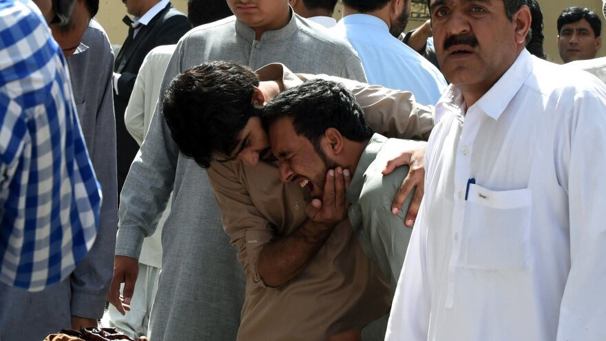 Pakistani journalists grieve over the body of a news cameraman after an explosion at a government hospital in Quetta on Monday.