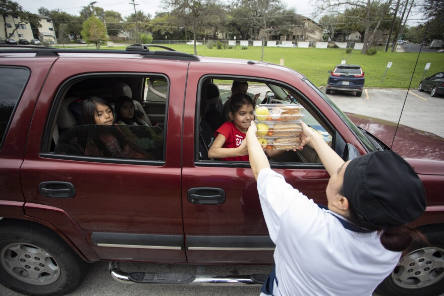 Isabel Santana and her children pick up food from Dawson Elementary School. Austin ISD offered families the option to pick up lunches after school was canceled over coronavirus concerns.