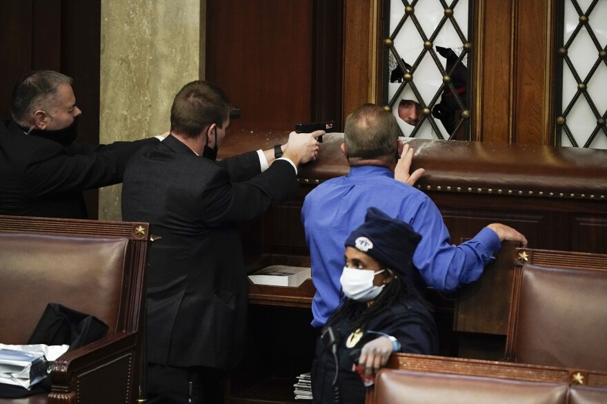 Police with guns drawn face off with protesters trying to break into the House chamber at the Capitol.